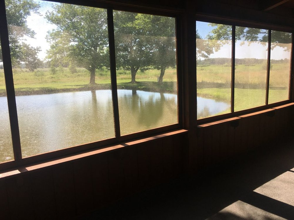Screened in porch has views of pond next to cabin