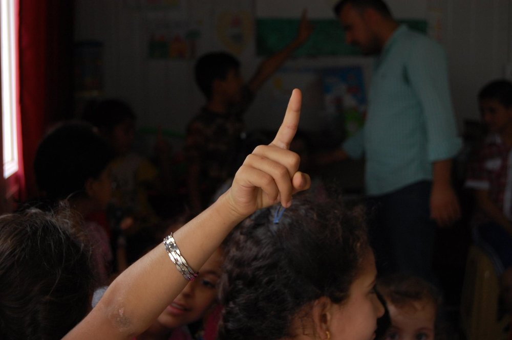A refugee girl raises her hand at Charmo Refugee Camp to be chosen to sing a song she learned in at small school in the camp.