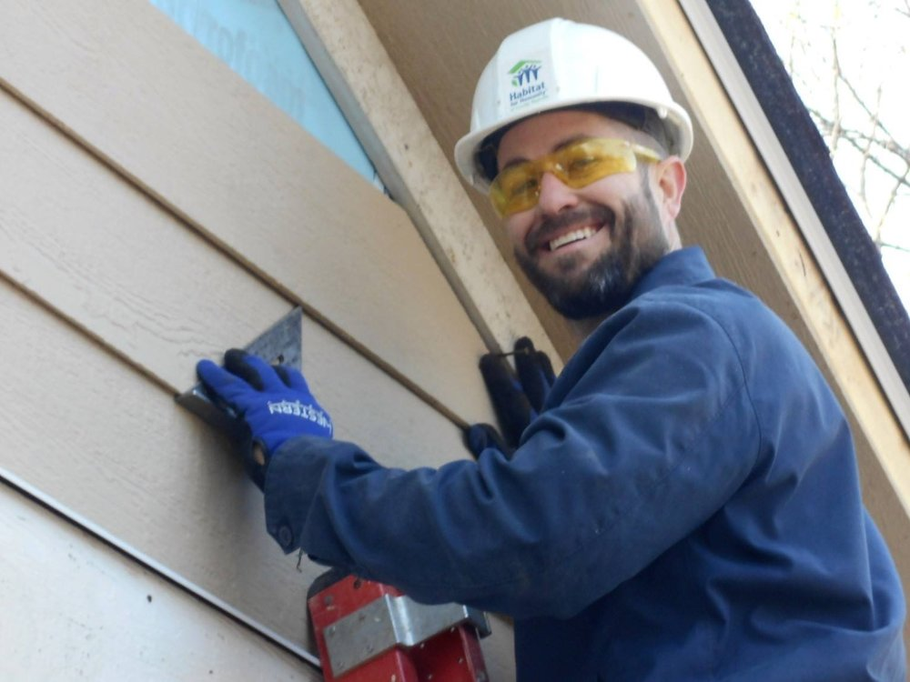 Clark, who is a former Habitat for Humanity President, hanging siding on a recent build.