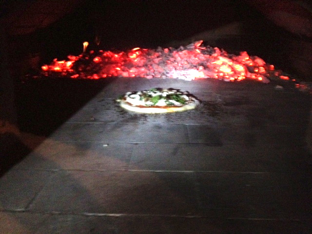 Our first pizza! Sorry for the bad picture - it is very hard to get good lighting inside a pizza oven.