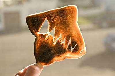 Burnt toast being held up with the word damn cut into it.