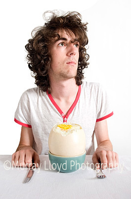 Teenage boy with ostrich egg in studio with white background.