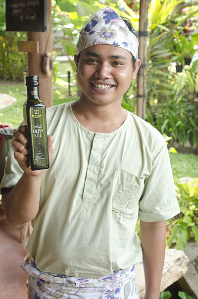Pa Putra from Swasti Eco Cottages holding Moutere organic olive oil from New Zealand