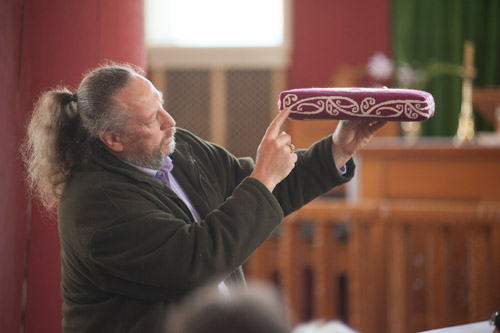 Andre Baker explains the hammerhead shark design in the kneeler cushions in Rangiatea Church