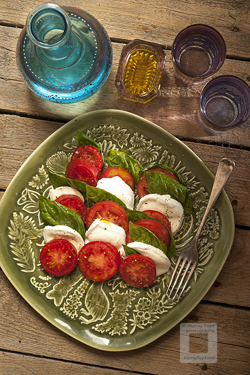Caprese salad photographed from above with coloured glass and green platter.