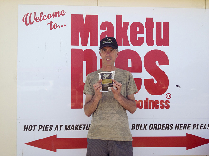 Portrait of man holding a Maketu pie in front of advertising design.
