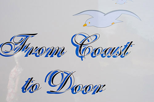 From coast to door signage on side of mobile fish and chip van.