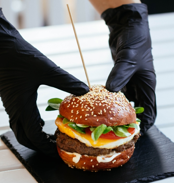 hands-gloves-holding-burger