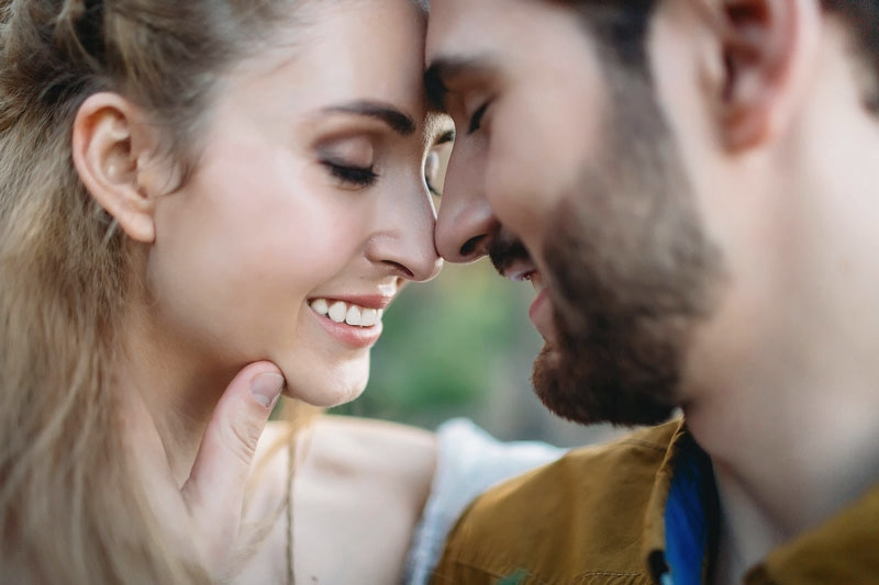 Close-up of couple with healthy smiles touching heads