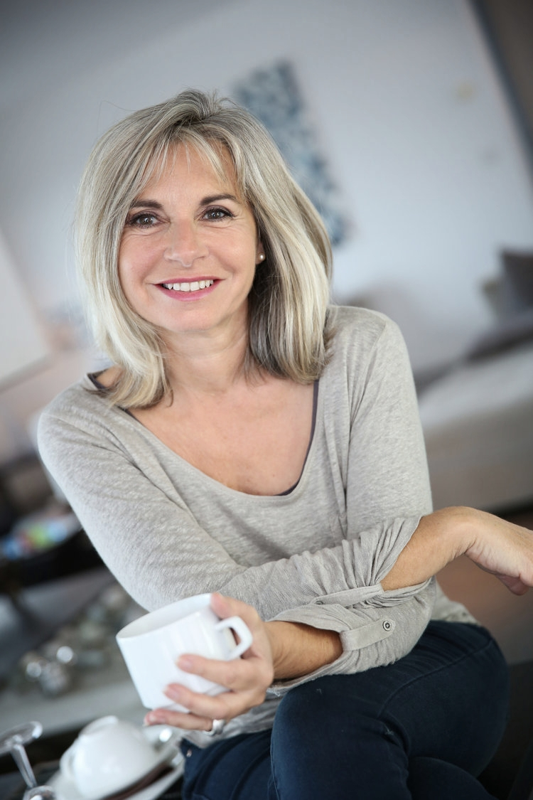 Attractive older lady enjoys a cup of coffee after finding new dental practice in Southampton