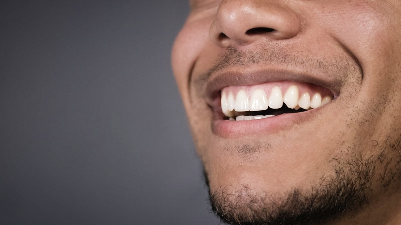 Close-up of man's straight teeth after braces in Southampton