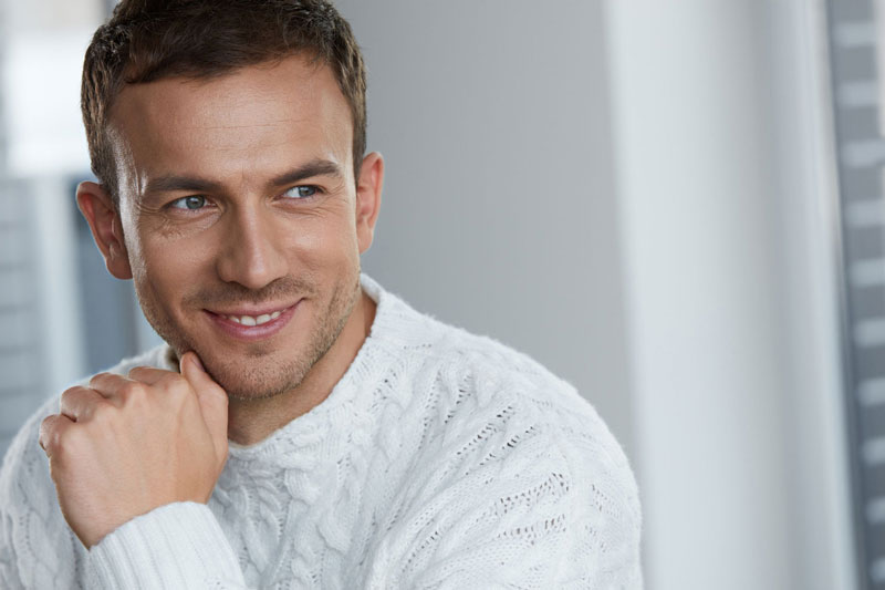 Attractive man in white jumper smiles after his derma roller skin treatment