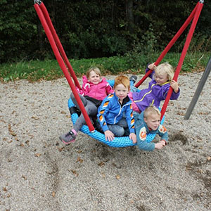 A group of children bundled together on one of our basket swings.