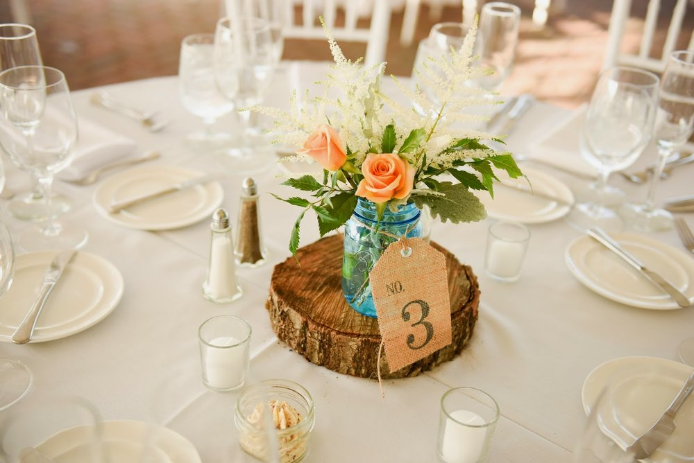 fruitlands museum : fall tent wedding : les fleurs : mkd photography : blue mason jar, white and caramel : tree trunk : wood slab : burlap table numbers
