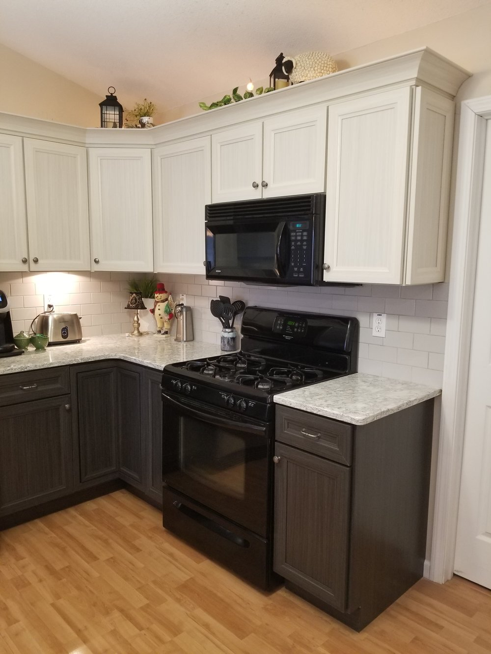 Homeowner fell in-love with the darker color doors loving the way it contrasted with their countertops.  To keep the kitchen from looking too dark they went lighter for the wall cabinets.