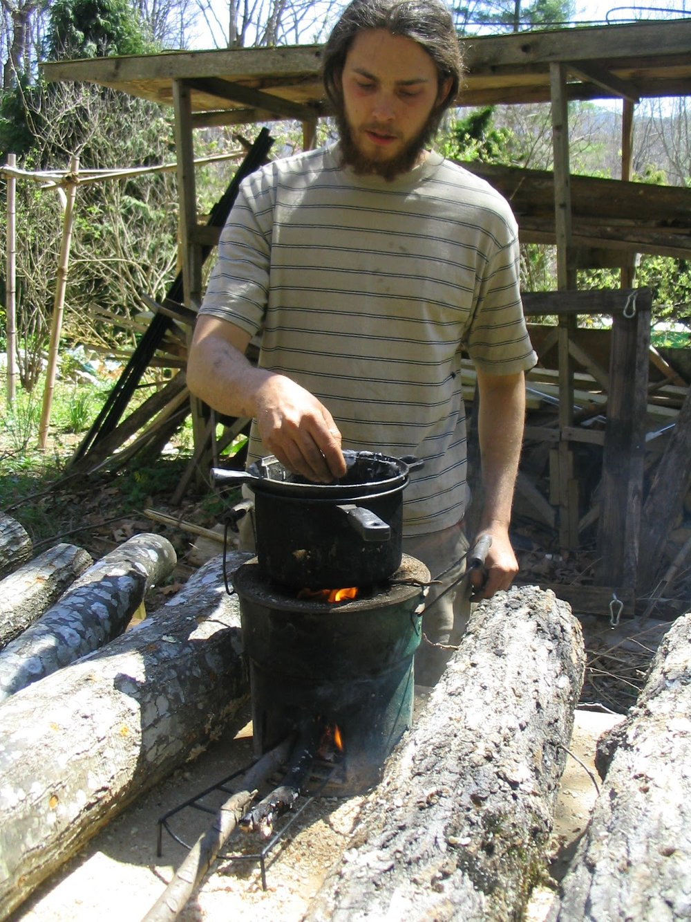 Ryan melts wax on the Rocket Stove to apply to the log.