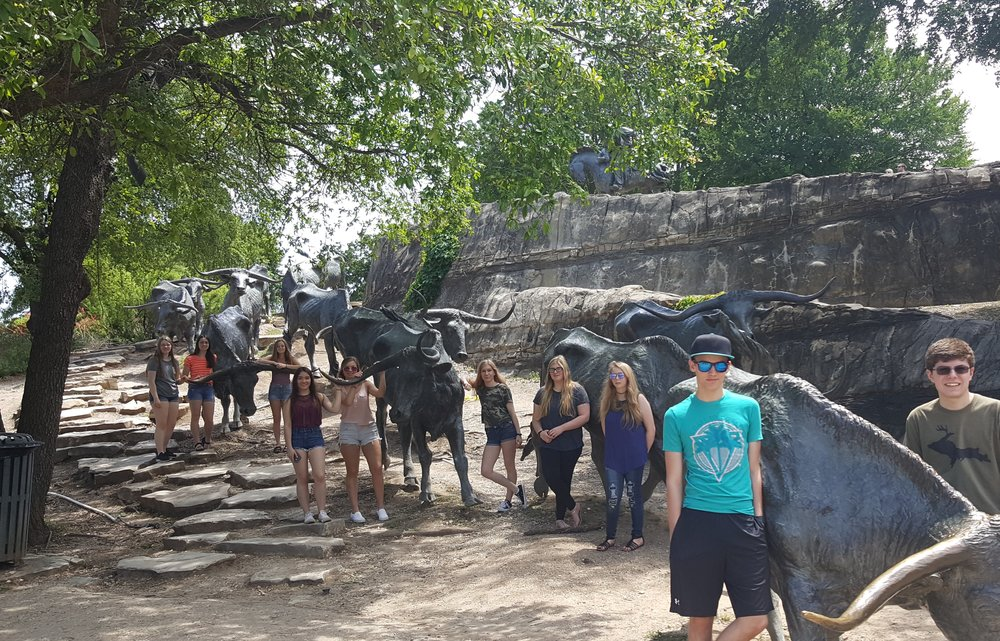 Westwood HS - 2018 NLC - Students with bronze sculptures at Pioneer Plaza in Dallas