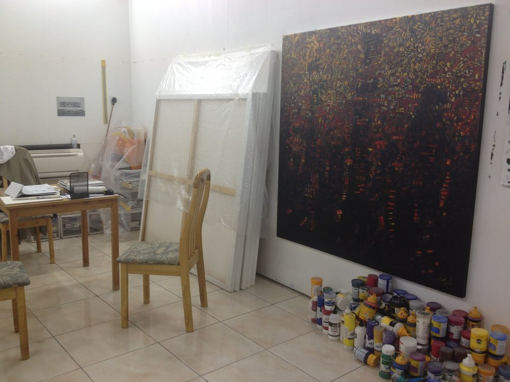 Paints piled high and large scale paintings at Mohammed Al Qassab's studio
