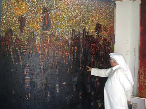 Mohammad Al Qassab with his painting in his studio in Sharjah