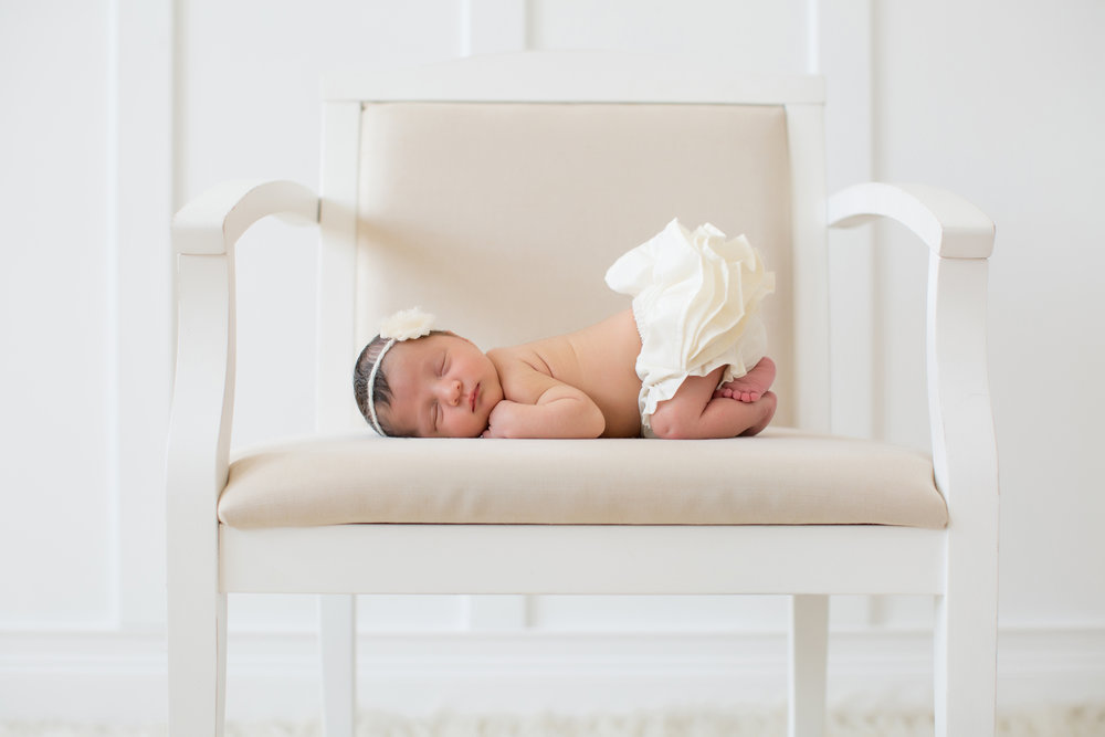 newborn-girl-on-chair-with-bloomers.jpg
