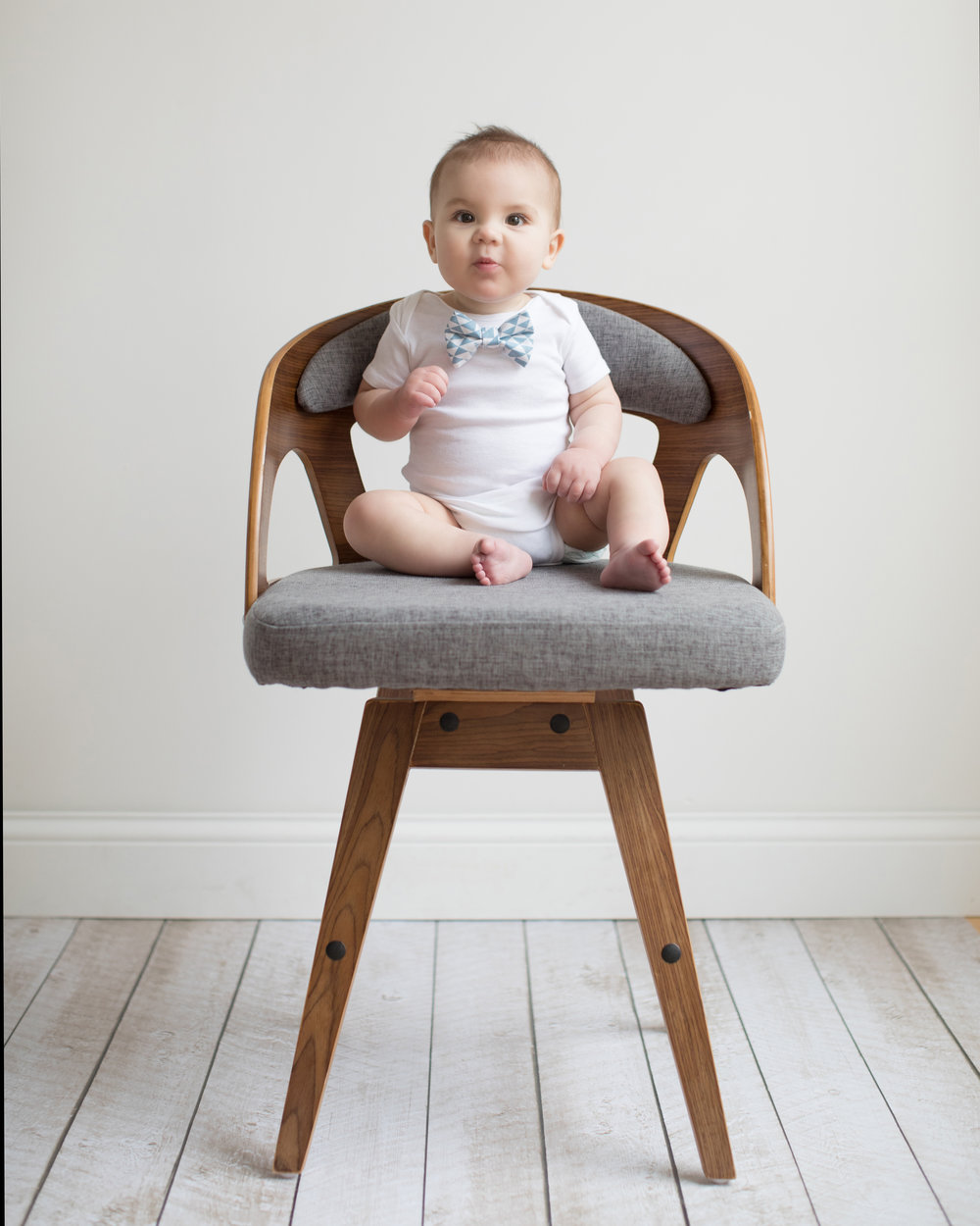 Baby boy in white onesie sitting on chair during natural light studio portrait session