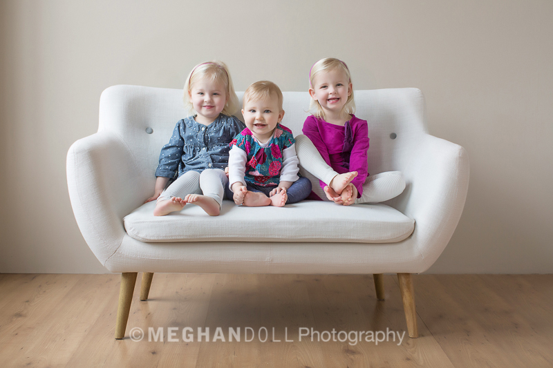 twin girls and baby sister on mod couch