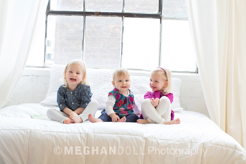three little girls sitting on bed