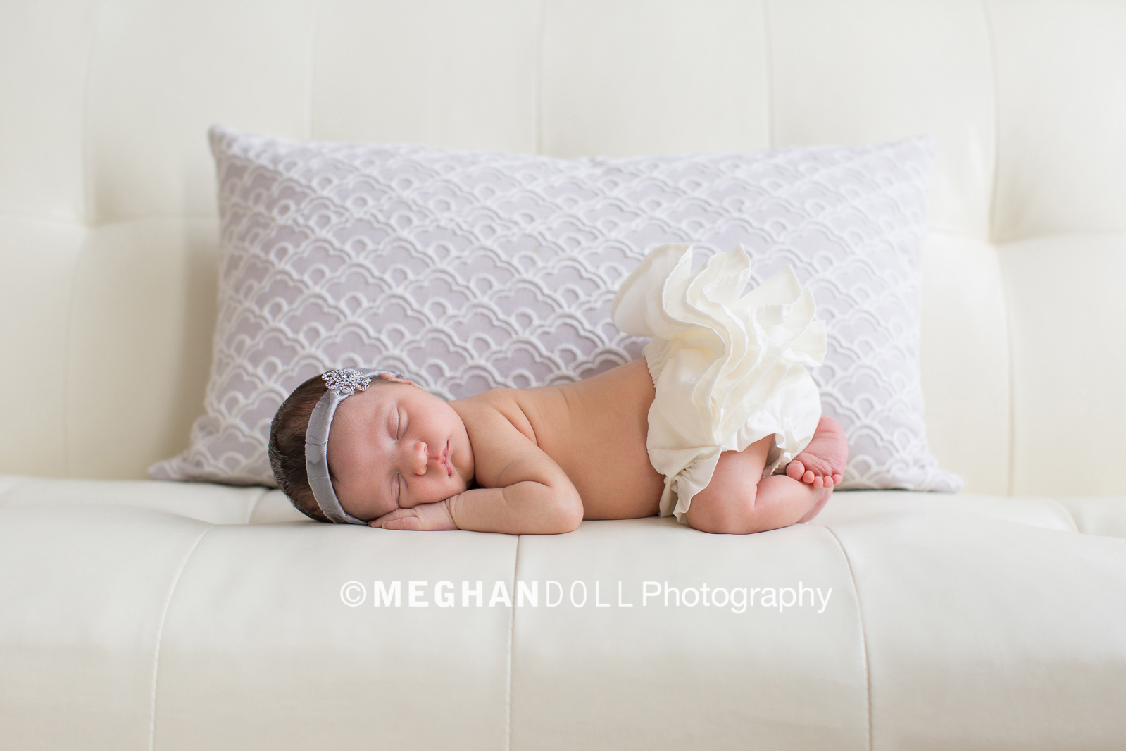 newborn baby in ivory ruffle bloomers sleeping on couch with delicate purple pillow behind her.