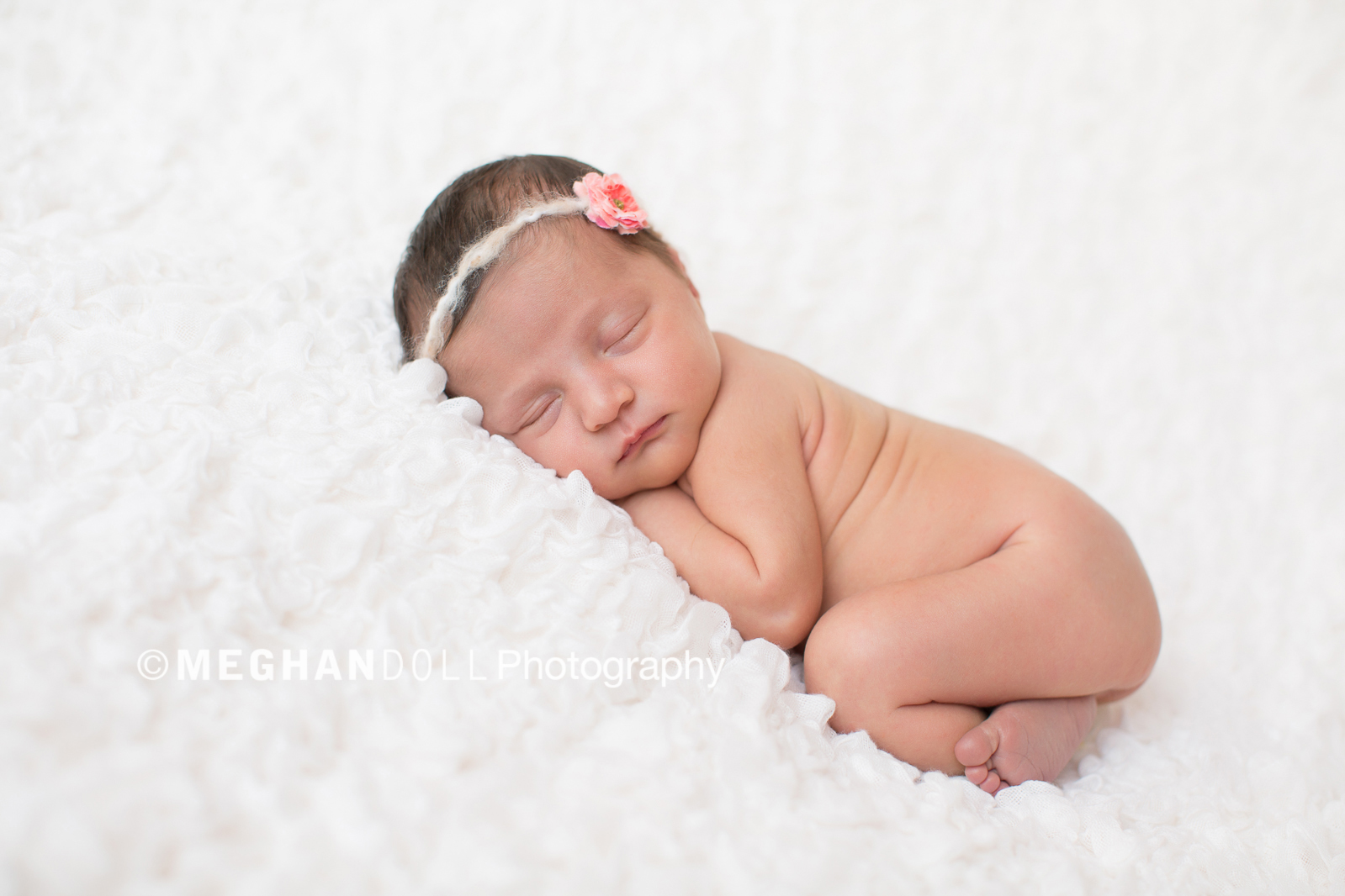 sweet naked little newborn girl sleeping soundly on her belly.