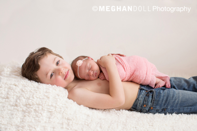 Sweet 5 year old boy wearing only jeans holding his newborn sister in a pick wrap on his chest.