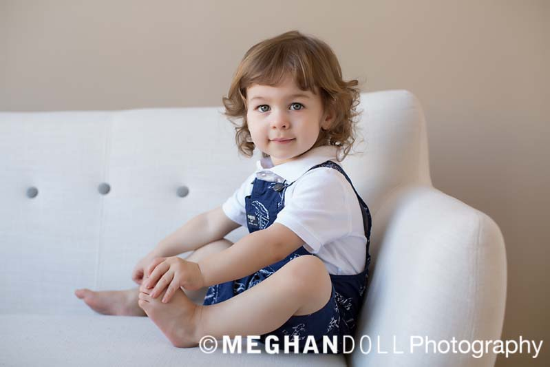little boy sitting on couch holding his toes with a sweet, shy expression on his face.