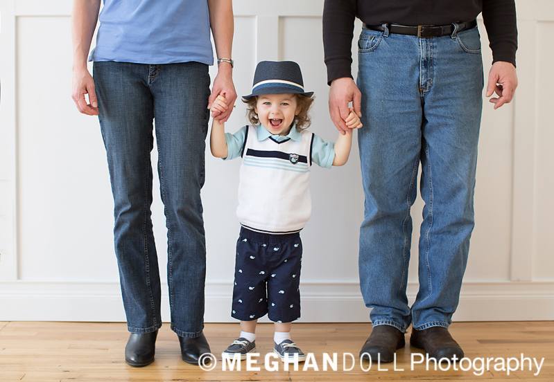 little boy holding mom and dads hands with a huge smile on his face. he is looking sharp in a preppy outfit complete with a fedora.