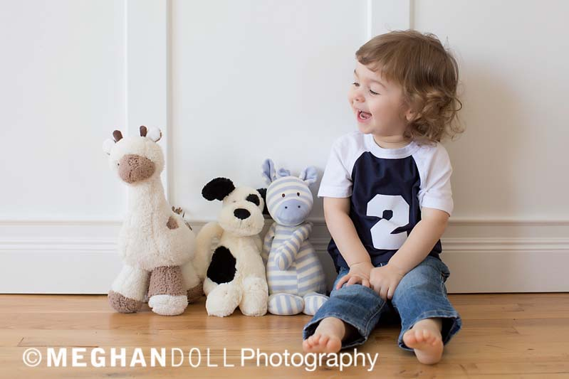 Little boy wearing a tee shirt stating he is two years old, sitting with his favorite stuffed animals having a conversation with them.