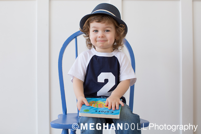 two year old boy with satisfied expression sitting on a blue chair holding a book.