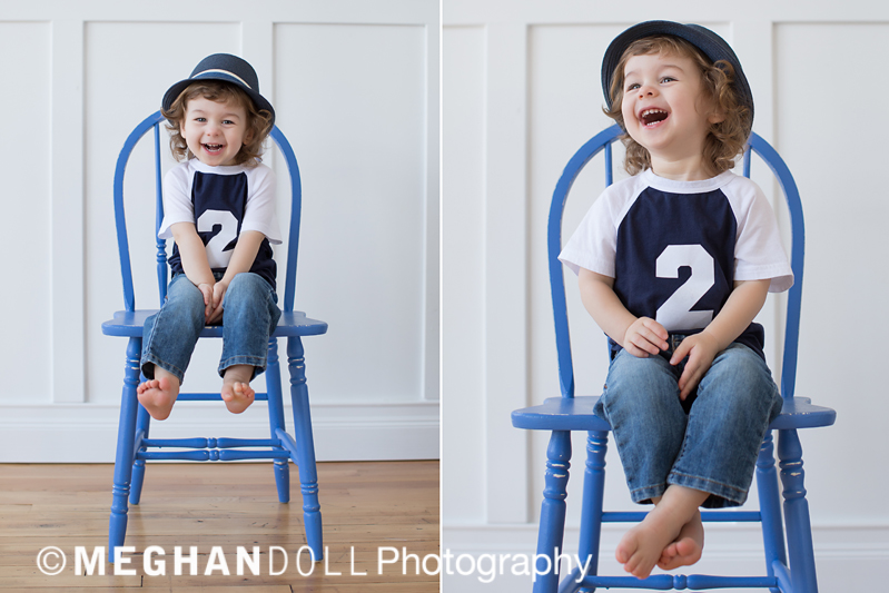 two year old child laughing and kicking up his toes wearing a fedora