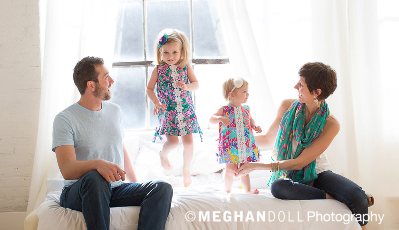 Colorfullly dressed family sitting on bed. Little girls are jumping on the bed.