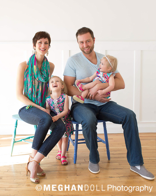 Portrait of two parents posing for the camera with two giggling kids with them.