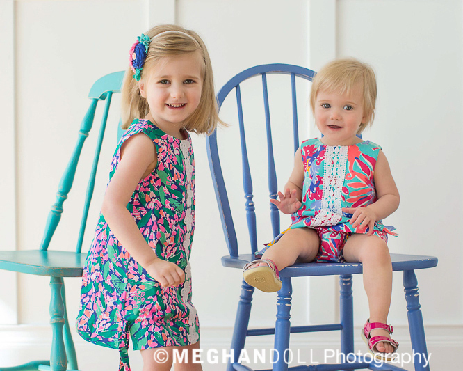 Little girls sitting on bright torquiose and blue chairs wearing colorful floral print dresses.