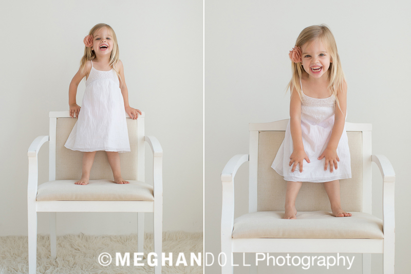 Three year old girl standing on chair being silly in a cute white dress.