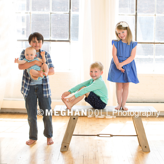 Four siblings standing, sitting, and holding the baby on a cool bench