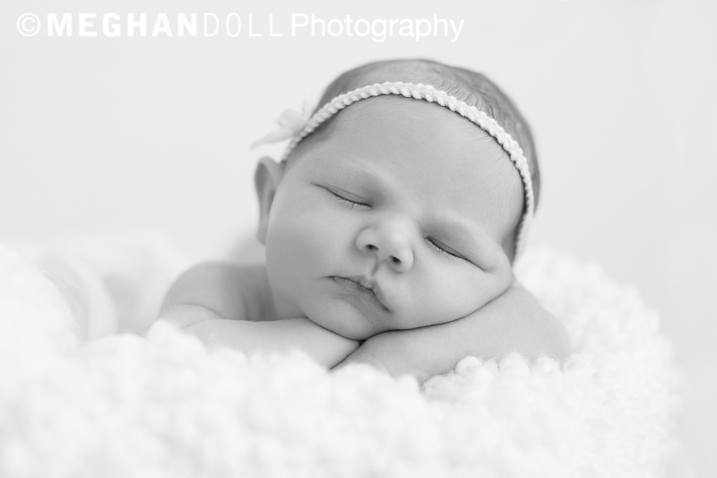 Angelic newborn girl sleeping on her arms with a halo headband in black and white.