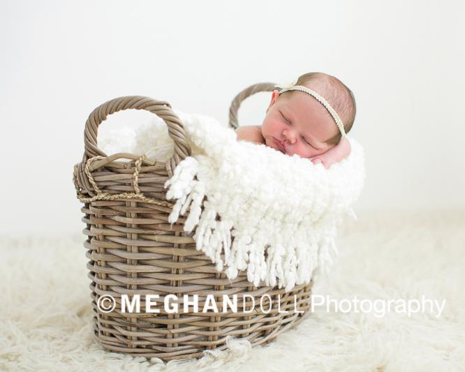 Sleeping baby in basket wearing halo headband.