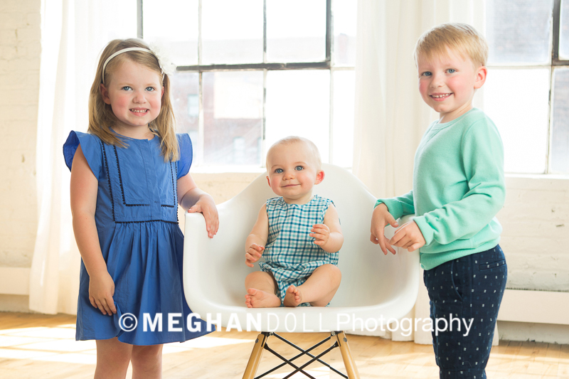 Two older siblings standing with baby brother sitting in chair in the middle of them.