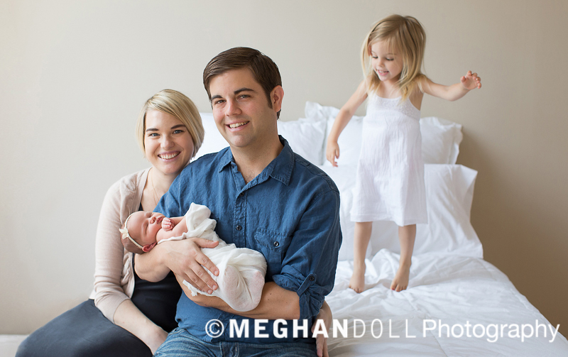 Mom and dad holding newborn baby girl while toddler jumps on bed.
