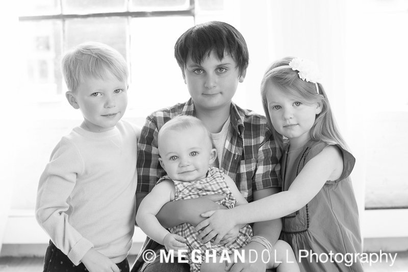 Black and white image of three older siblings holding a little baby with small smiles.