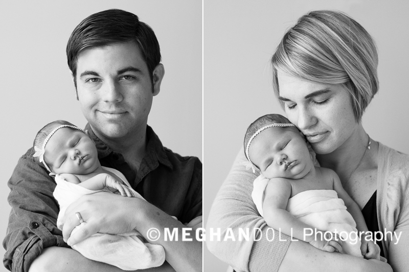 New parents proudly holding their newborn baby girl in black and white.