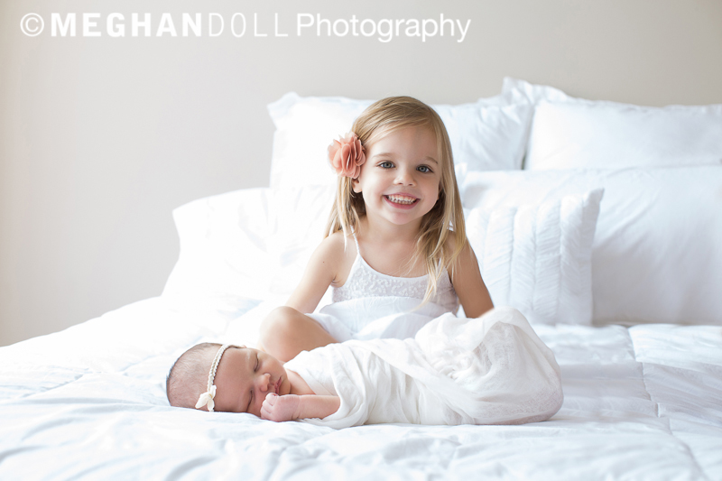 Proud big sister sitting on bed with sleeping newborn.