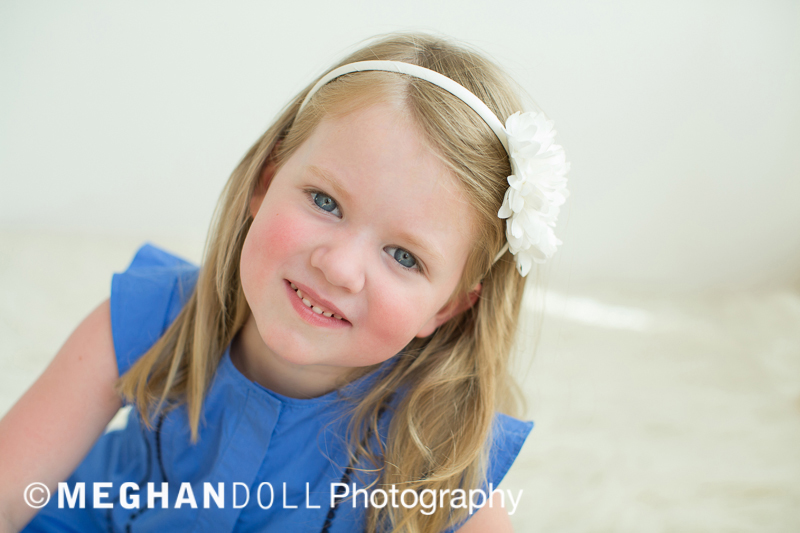 Little girl in blue dress with white headband smiling.
