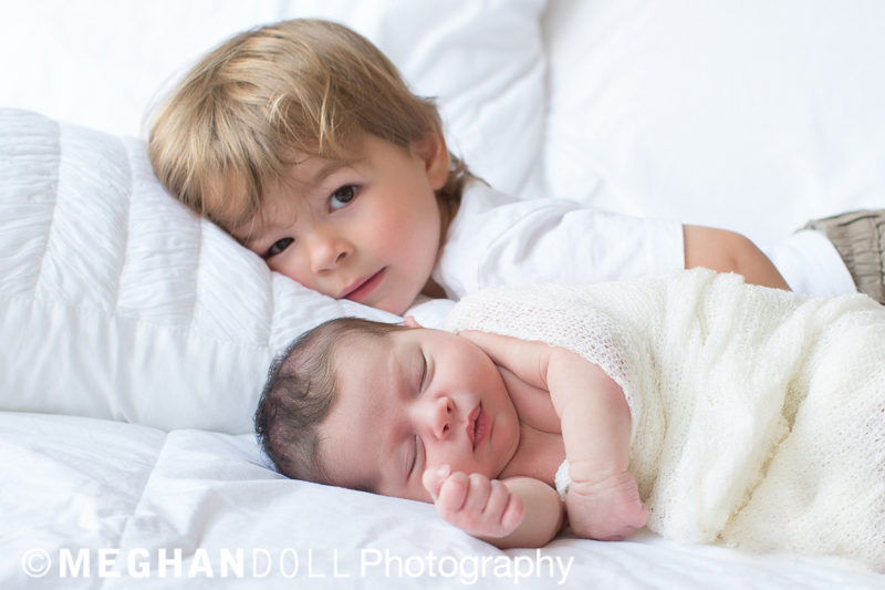 little boy snuggling next to newborn sister, peeking sweetly out from behind her.