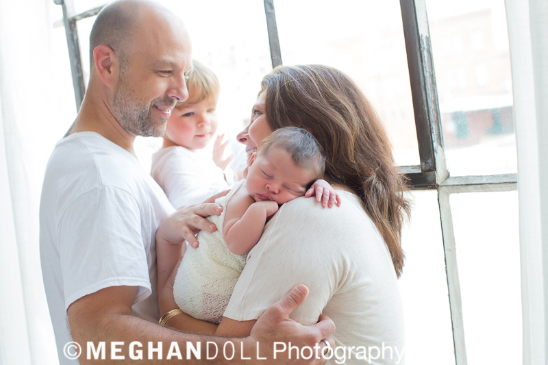 Family of four standing by the window looking at each other with love. Mom is holding a newborn baby.